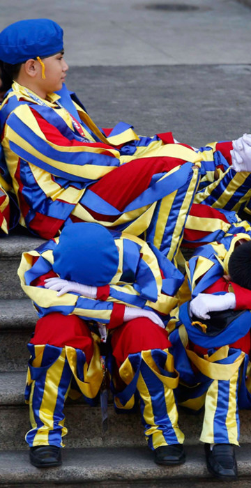 Image: Schoolchildren dressed as Swiss Guards rest as they wait for the arrival of Pope Francis outside the Manila Cathedral in Manila