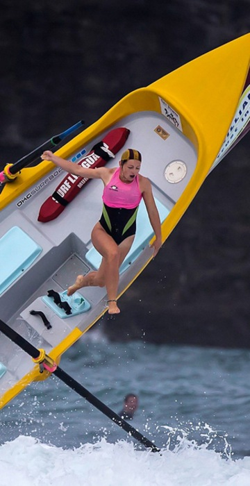 Image: Alison Cragie, a member of a women's surf boat crew, is thrown from the boat by a breaking wave during a race in the Day of Giants Surf Boat Competition being held at Piha Beach, located west of Auckland