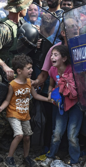 Image: Macedonian police clash with refugees at blocked border