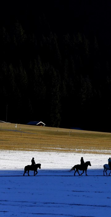 Image: People on horses make their way over snow covered meadows