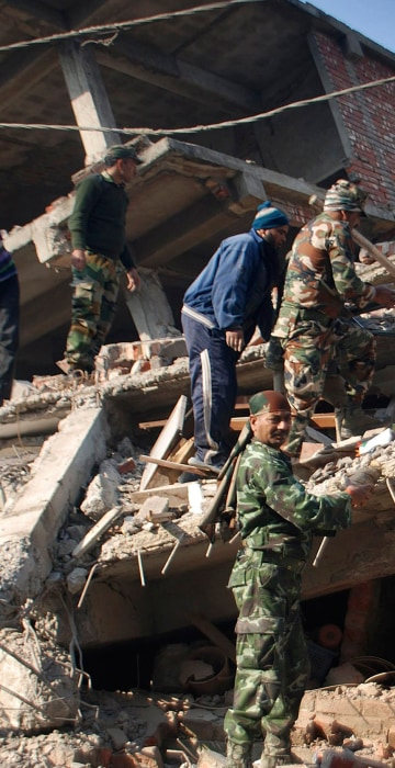 Image: Locals help Indian soldiers remove debris from a damaged building
