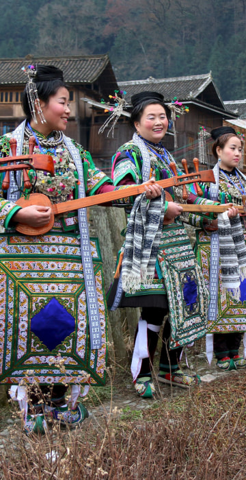 "Image: Ethnic Dong women wearing traditional costumes, hold ""pipas"", a traditional instrument"