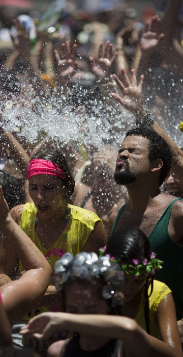 """Image: People cool off in water during the """"Escravos da Maua"""" block party"""