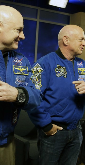 NASA astronaut Scott Kelly, left, and his identical twin Mark, a retired NASA astronaut, stand together before a news conference in Houston. Scott Kelly set a U.S. record with his 340-day mission to the International Space Station.