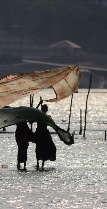 Image: Indian women dry their saris after taking a dip at Sangam
