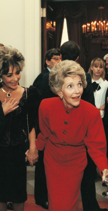Nancy Reagan tugs on Ronald's coat as he talks with Tom Selleck with Elizabeth Taylor in tow on Jan. 20, 1985.