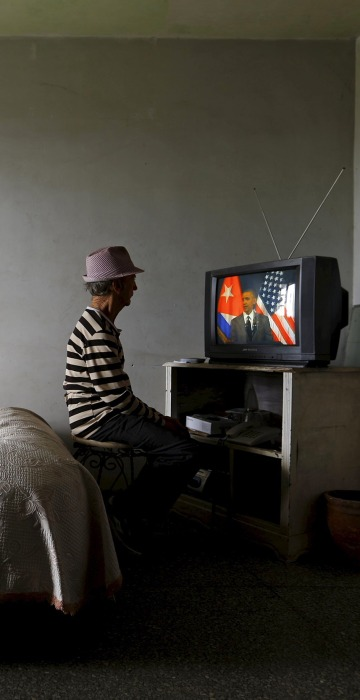 Image: A man watches on television as U.S. President Barack Obama delivers a speech at the Gran Teatro de la Habana Alicia Alonso in Havana