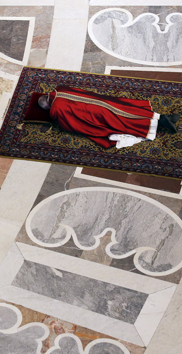 Image: Pope Francis lies as he prays during the Celebration of the Lord's Passion in Saint Peter's Basilica at the Vatican