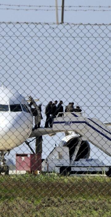 Image: Passengers evacuate a hijacked EgyptAir Airbus 320 plane at Larnaca airport