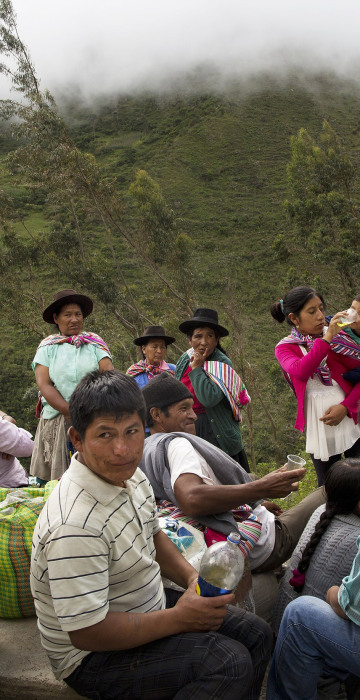 Image: People eat and visit during a burial for over 30 villagers killed more than two decades ago