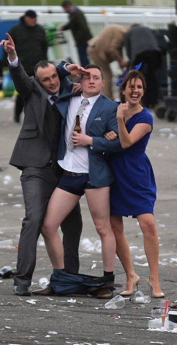 Image: A man plays to the cameras as racegoers make their way home at the end of Ladies Day