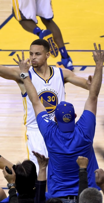 Image: Stephen Curry (R) reacts after making a three-point shot