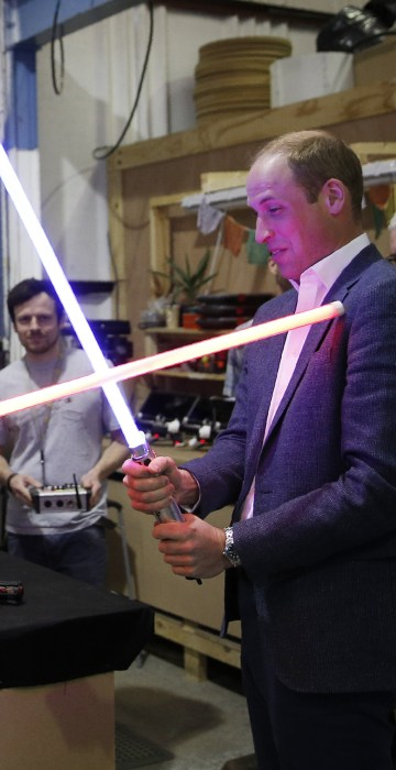 Image: Britain's Prince William, right, and Prince Harry use light sabers