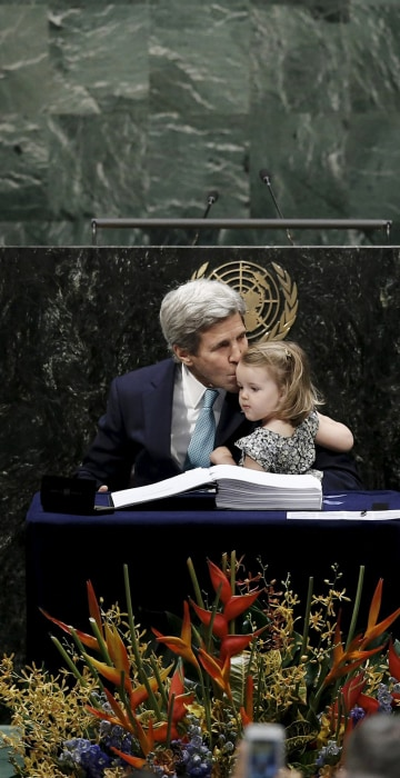 Image: U.S. Secretary of State Kerry holds his granddaughter as he signs the Paris Agreement on climate change at United Nations Headquarters in New York
