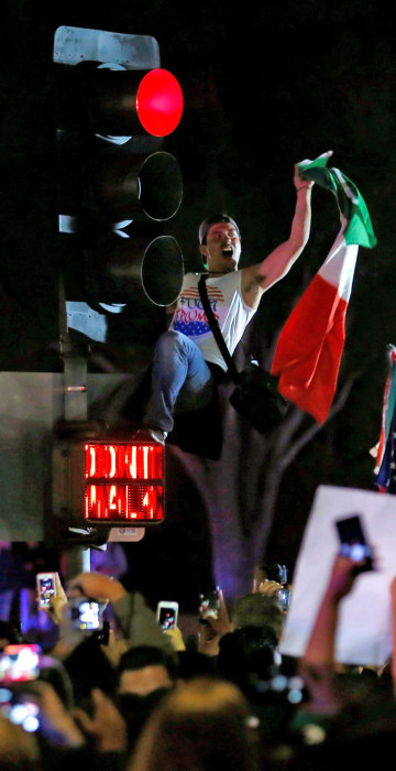 Image: A demonstrator climbs a traffic light outside Republican U.S. presidential candidate Donald Trump's campaign rally in Costa Mesa