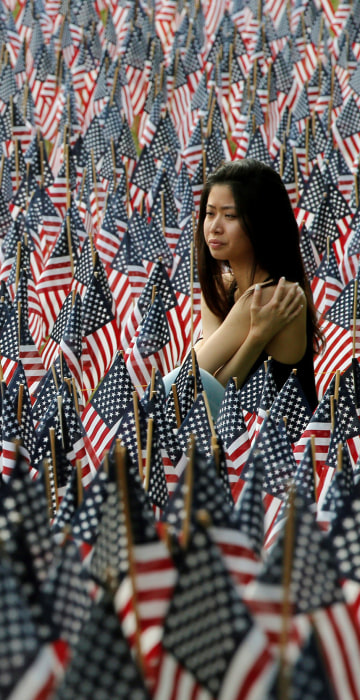 Image: A woman sits at the edge of the field of United States flags displayed by the Massachusetts Military Heroes Fund on the Boston Common in Boston