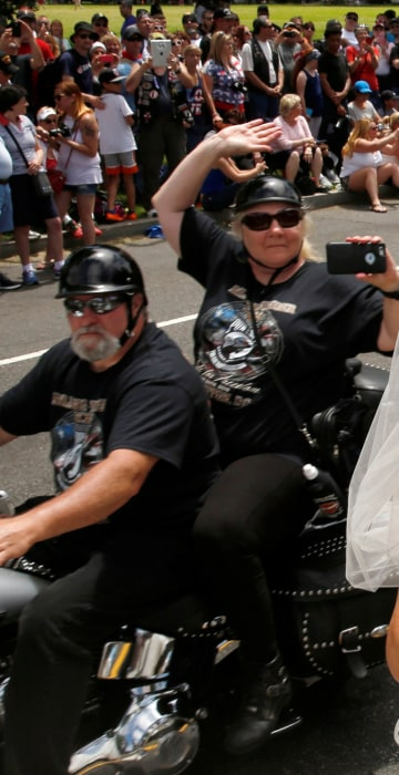 Image: Tim Chambers kisses his new bride Lorraine Heist as riders pass by during the Rolling Thunder motorcycle rally in Washington