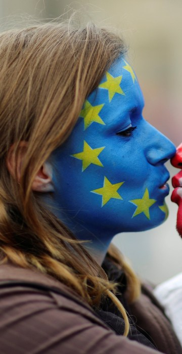 Image: Two activists with the EU flag and Union Jack painted on their faces kiss each other in front of Brandenburg Gate to protest against Brexit in Berlin