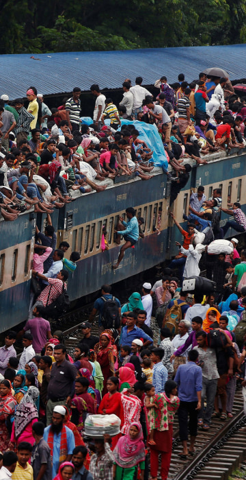 Image: People climb to board an overcrowded passenger train as they travel home to celebrate Eid al-Fitr festival, which marks the end of the Muslim holy fasting month of Ramadan, at a railway station in Dhaka