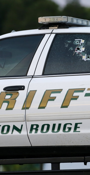 Image: An East Baton Rouge Sheriff vehicle is seen with bullet holes in its windows near the scene where police officers were shot, in Baton Rouge