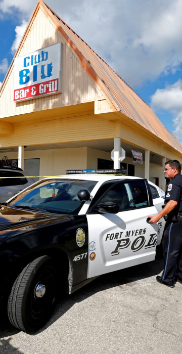 Image: A Fort Myers police officer is seen at a parking lot of Club Blu after a shooting in Fort Myers