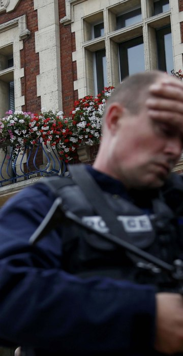 Image: A policeman secures the position in front of the city hall after two assailants had taken five people hostage in the church at Saint-Etienne-du -Rouvray near Rouen in Normandy