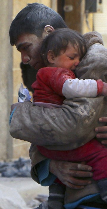 Image: A boy holds his baby sister saved from under rubble, who survived what activists say was an airstrike by forces loyal to Syrian President Bashar al-Assad in Masaken Hanano in Aleppo