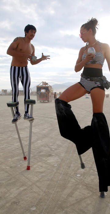 Image: Katapult Sandra and Divine Mustache, using their Playa names, dance on stilts on Monday.