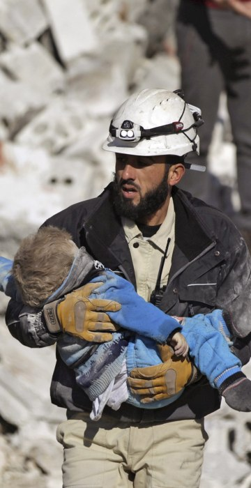 Image: A civil defence member carries a dead child in a site hit by what activists said were airstrikes carried out by the Russian air force in the rebel-controlled area of Maaret al-Numan town in Idlib province, Syria