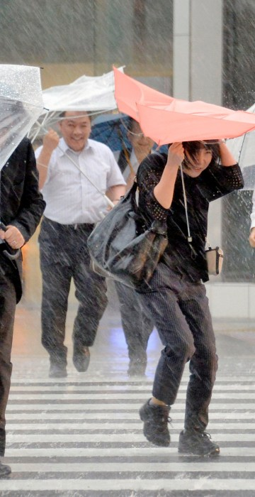 Image: Pedestrians holding umbrellas struggle against strong wind and heavy rains caused by Typhoon Malakas in Nagoya, central Japan