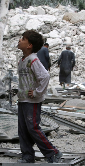 Image: A boy inspects a damaged site after airstrikes on the rebel held Tariq al-Bab neighbourhood of Aleppo