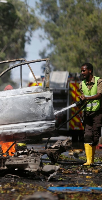 Image: A firefighter tries to extinguish the fire from the wreckage of a burning vehicle after it exploded in front of the Blue Sky restaurant in Mogadishu, Somalia