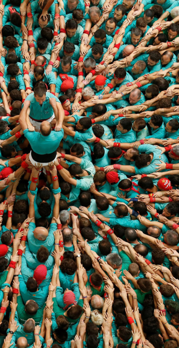 """Image: Castellers de Vilafranca start to form a human tower called \""""castell\"""" during a biannual competition in Tarragona city"""