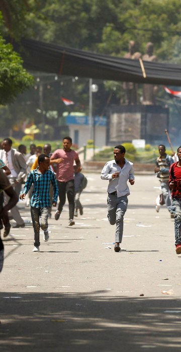Image: Protesters run from tear gas being fired by police during Irreecha, the thanks giving festival of the Oromo people in Bishoftu town of Oromia region, Ethiopia