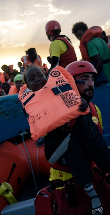 Image: A child from African origin is rescued from a distressed vessel by a member of Proactiva Open Arms NGO in the mediteranean