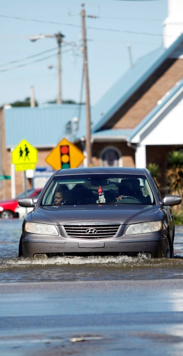 Image: A car navigates a flooded street off Highway 41 in Lumberton