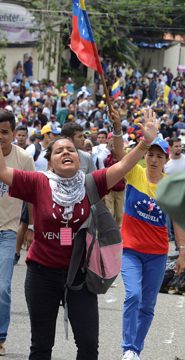 Image: Demonstrators shout slogans in front of Venezuelan National Guard members during a rally demanding a referendum to remove Venezuela's President Maduro in San Cristobal