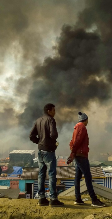 """Image: Migrants stand on a hill overlooking the \""""Jungle\"""" migrant camp in Calais"""