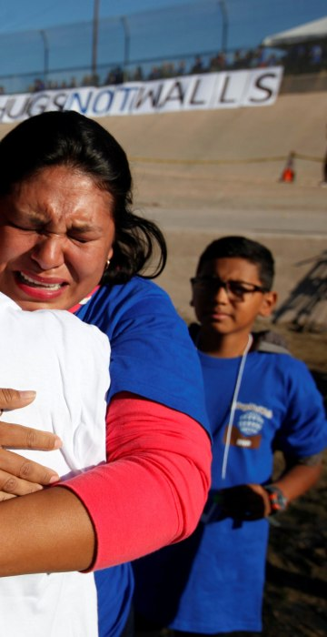 Image: Relatives separated by deportation and immigration hug at the border during a brief reunification meeting at the banks of the Rio Bravo, a natural border between U.S. and Mexico