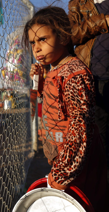 Image:  An Iraqi refugee girl waits with her parents to buy food from a local vendor behind the fence of the Khazir refugee camp near the Kurdish checkpoint of Aski Kalak