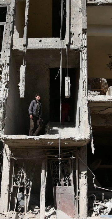 Image: People inspect a damaged building after strikes yesterday on the rebel held besieged city of Douma, in the eastern Damascus suburb of Ghouta