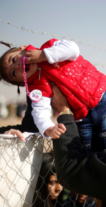 Image: A displaced Iraqi man, who fled the Islamic State stronghold of Mosul, holds his daughter to be seen by her grandmother through a fence at Khazer camp