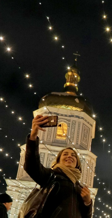 Image: People take pictures next to an illuminated Christmas tree in front of the St. Sophia Cathedral in central Kiev, Ukraine, Dec. 21.