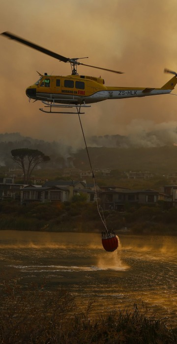 Image: Firefighting helicopters battle a vegetation fire fanned by gale force winds raging in the Helderberg mountains around Somerset West, South Africa on Jan. 4.