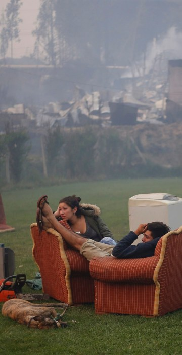 Image: A young couple rest in a football field after a forest fire devastated Santa Olga