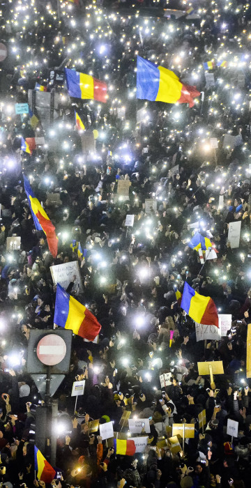 Image: Tens of thousands of people shine lights from mobile phones and torches during a protest.