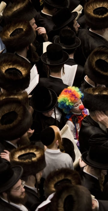 Image: An Ultra Orthodox Jewish child dressed as a clown stands among men reading from the Book of Esther during a prayer for the Jewish Holiday of Purim in the Mea Shaarim neighborhood in Jerusalem, Israel.