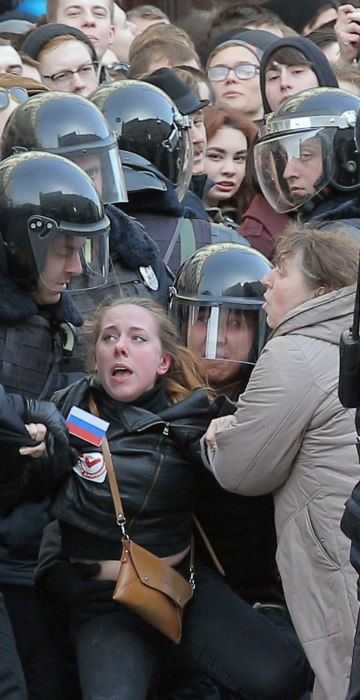 Image: Russian riot policemen detain a demonstrator.