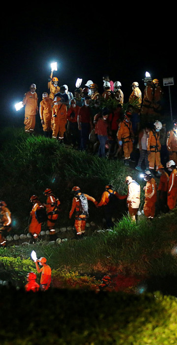 Image: Rescue members walk during the burial of a companion who died after flooding and mudslides caused by heavy rains lead several rivers to overflow, pushing sediment and rocks into buildings and roads, in Mocoa