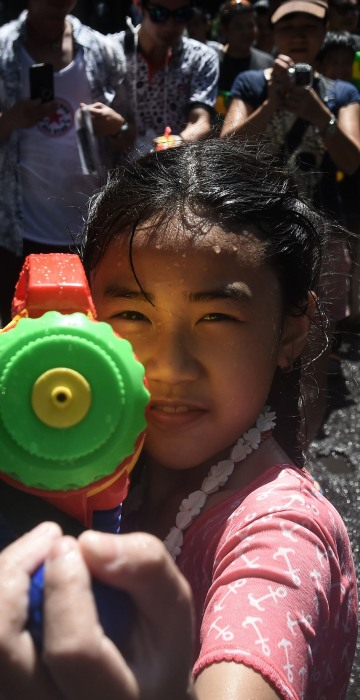 Image: A girl aims a water pistol at the camera during Songkran